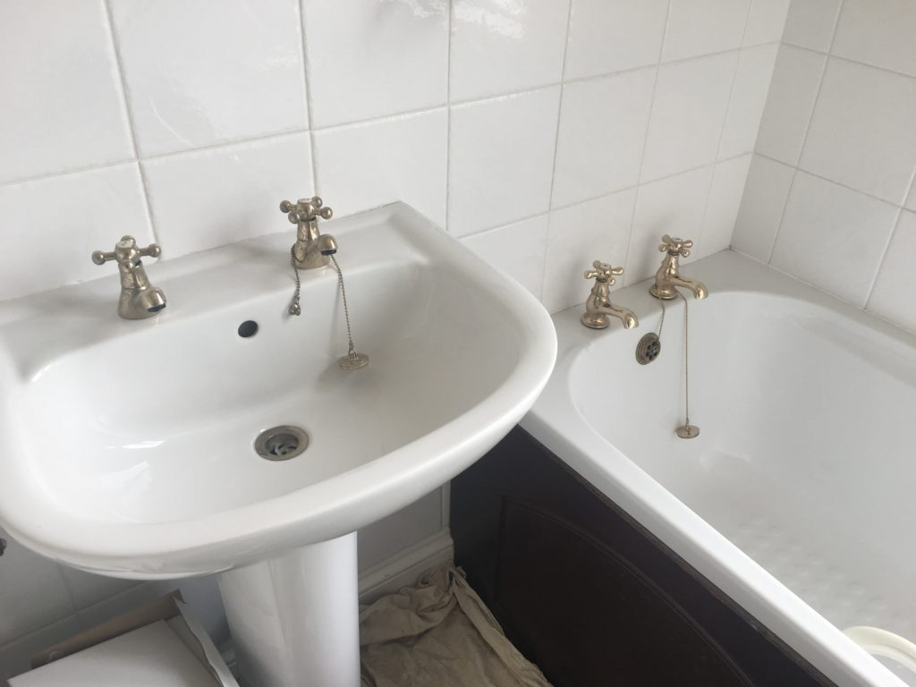 White sink and bath with gold taps against a white tiled wall