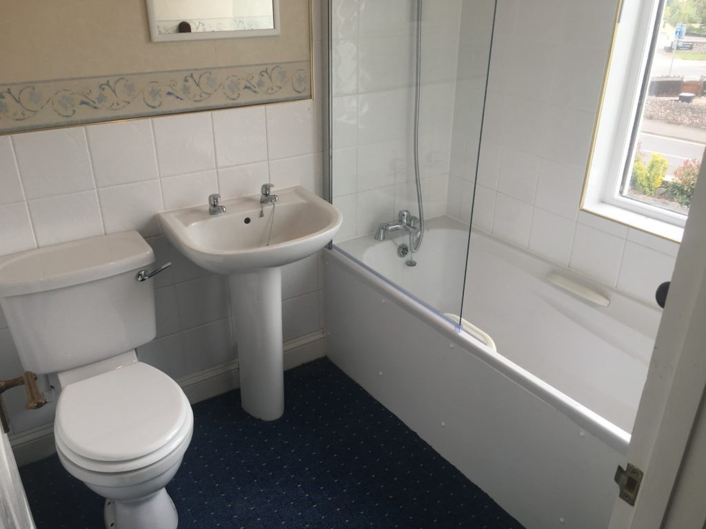 Toilet, sink and bath with shower above against a white tiled wall with a clear glass shower screen