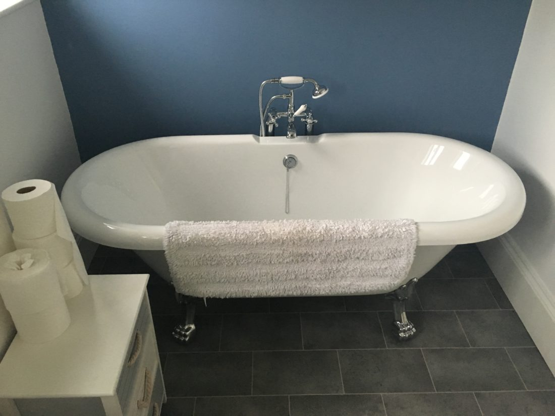 White bath with chrome feet and taps set against a blue feature wall for a bathroom remodel in Teignmouth