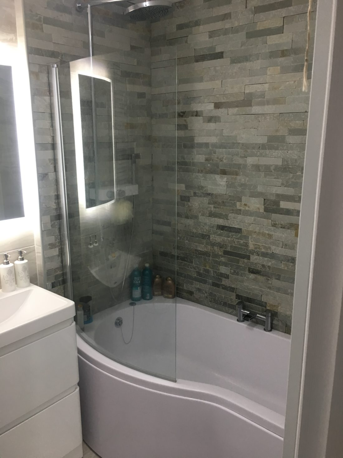 Backlit mirror next to a power shower surrounded by grey slate wall tiles