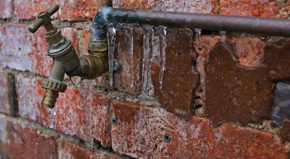 Red brick wall with a metal frozen pipe and tap attached with icicles hanging off it